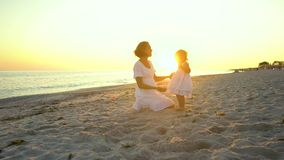 Den unga härliga kvinnan går med hennes lilla dotter på kusten på solnedgången De är lyckliga Konturer mot stock video