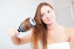 Den unga härliga kvinnan gör frisyren Royaltyfria Foton