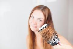 Den unga härliga kvinnan gör frisyren Royaltyfri Foto
