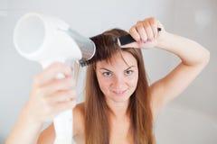 Den unga härliga kvinnan gör frisyren Royaltyfri Fotografi
