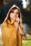 Den unga härliga kvinnan ha på sig scarfen Arkivbild
