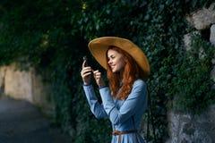 Den unga härliga kvinnan i en hatt gör ett foto på telefonen i en gränd i staden arkivbilder