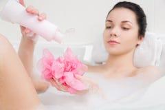 Den unga kvinnan i ett bad med skummar snyltar räcker in Arkivbild