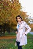 Den unga härliga kvinnan i höst parkerar att posera Arkivfoto