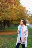 Den unga härliga kvinnan i höst parkerar att posera Arkivbild