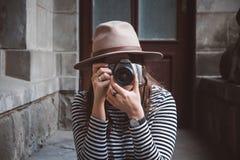 Den unga härliga kvinnan i hatt tar bilden med den gammalmodiga kameran, utomhus arkivfoton