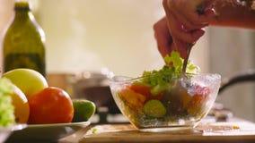 Den unga härliga kvinnan i hem- kläder lagar mat i köket Hon gör någon ny sallad med grön grönsallat stock video