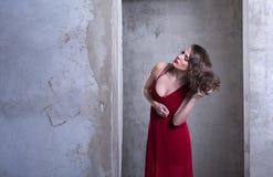 Den unga härliga kvinnan i röd klänning rätar ut hennes hår Arkivfoton