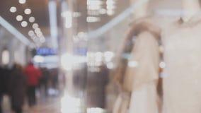 Den unga härliga kvinnan i shoppar fönstret som hennes framsida reflekteras in shoppar fönstret lager videofilmer