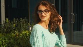 Den unga härliga kvinnan i solglasögonleenden och vänder hennes framsida åt sidan lager videofilmer