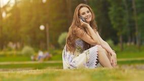 Den unga härliga kvinnan i sommarklänning med långt hårsammanträde på gräs i gräsplan parkerar och tala på telefonen som ler royaltyfri bild