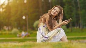 Den unga härliga kvinnan i sommarklänning med långt hårsammanträde på gräs i gräsplan parkerar och tala på telefonen som ler royaltyfria bilder