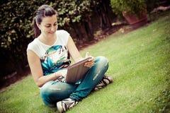 Den unga härliga kvinnan lägger på gräsplan sätter in royaltyfri bild
