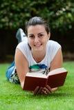 Den unga härliga kvinnan lägger på gräsplan sätter in fotografering för bildbyråer