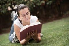 Den unga härliga kvinnan lägger på gräsplan sätter in royaltyfri foto