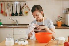 Den unga härliga kvinnan lagar mat i köket fotografering för bildbyråer