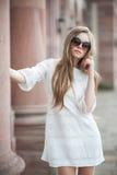 Den unga härliga kvinnan med långt hår i den vita klänningen bär s Royaltyfria Bilder