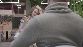 Den unga härliga kvinnan med rött lockigt hår äter Caesar sallad i ett kafé och sitter mitt emot en man arkivfilmer