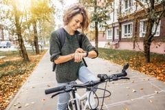 Den unga härliga kvinnan på en cykel använder en smartwatch, navigering royaltyfria foton