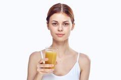 Den unga härliga kvinnan på vit bakgrund rymmer ett exponeringsglas av nytt sammanpressad fruktsaft, bantar, kondition som bantar Arkivfoton