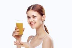 Den unga härliga kvinnan på vit isolerad bakgrund rymmer ett exponeringsglas av fruktsaft, bantar, kondition som bantar Royaltyfri Foto