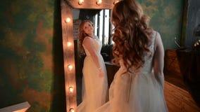 Den unga härliga kvinnan putsar nära spegeln med lampor stock video