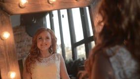 Den unga härliga kvinnan putsar nära spegeln med lampor lager videofilmer