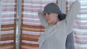Den unga härliga kvinnan sätter på den gråa sjaletten på hennes head anseende för spegeln hemma arkivfilmer