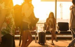 Den unga härliga kvinnan sitter i flygplats med smartph för lopppåsebruk arkivfoto