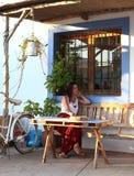 Den unga härliga kvinnan sitter i terrassen av en stilfull stång i Formentera, Balearic Island, Spanien Royaltyfri Fotografi