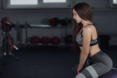 Den unga härliga kvinnan sitter på konditionboll i idrottshall royaltyfria bilder