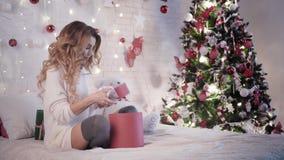 Den unga härliga kvinnan slår in julgåvor som sitter på sängen nära julgranen stock video