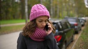 Den unga härliga kvinnan som använder hennes mobiltelefon på en bakgrund av gula och röda sidor, medan gå i hösten, parkerar lager videofilmer