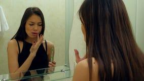 Den unga härliga kvinnan som borstar hennes tänder i badrum, och stoppet på grund av en tand smärtar arkivfilmer