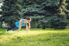 Den unga härliga kvinnan som gör sportövningar i, parkerar royaltyfria bilder