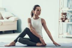 Den unga härliga kvinnan som gör yoga, poserar hemma royaltyfri foto