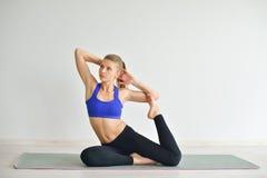 Den unga härliga kvinnan som gör yoga, poserar inomhus på grå bakgrund Flicka som öva hennes kropp i idrottshall Royaltyfria Bilder