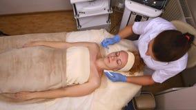 Den unga härliga kvinnan som ligger på den kliniska tabellen, cosmetologisten, gör henne en ansikts- electro-stimulans massage arkivfoton