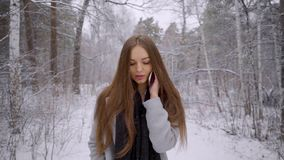 Den unga härliga kvinnan som talar på hennes mobiltelefon över snöig bakgrund, går utomhus i en vinter parkerar långsamt arkivfilmer