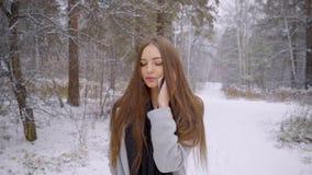 Den unga härliga kvinnan som talar på hennes mobiltelefon över snöig bakgrund, går utomhus i en vinter parkerar långsamt stock video