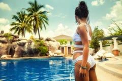 Den unga härliga kvinnan som tycker om sommarsemester på den tropiska ön Bali och, tycker om ferier på simbassängen Arkivbilder