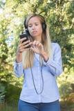 Den unga härliga kvinnan som väljer musik för att koppla av in, parkerar Royaltyfri Foto