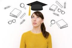 Den unga härliga kvinnan tänker om utbildning på affärssc Arkivfoto