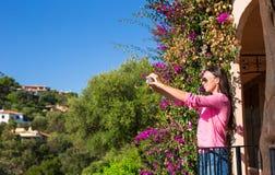 Den unga härliga kvinnan tar fotoet på hennes telefon på Arkivbild