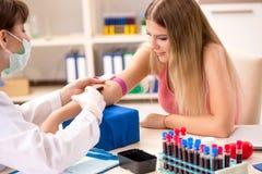 Den unga härliga kvinnan under tillvägagångssätt för provtagning för blodprov arkivbild