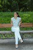 Den unga härliga kvinnan vilar på en parkerabänk unga vuxen människa Arkivbilder