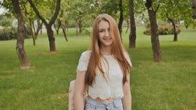 Den unga härliga kvinnliga studenten med långt hår med en ryggsäck på henne går tillbaka i parkera Vila under studie stock video