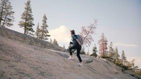 Den unga härliga kvinnliga turisten med ryggsäcken som bara fotvandrar och att klättra en jätte, vaggar på Yosemite nationalparku lager videofilmer