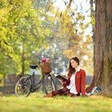 Den unga härliga kvinnlign med hennes cykel som läser en roman parkerar in Arkivbilder
