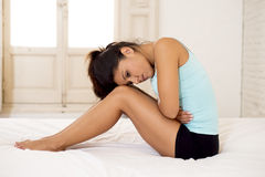 Den unga härliga latinamerikanska kvinnainnehavbuken som lider menstruations- period, smärtar Royaltyfria Bilder
